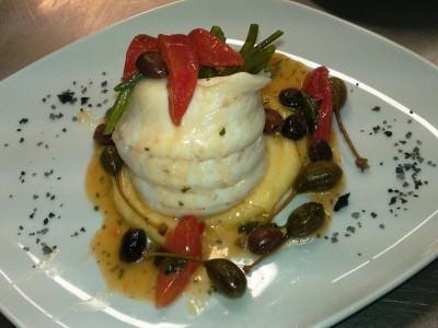 Filetto di branzino cotto al vapore posato su vellutata di patate con filetti di pomodorino, olive taggiasche, fiori di capperi di Pantelleria e sale nero
